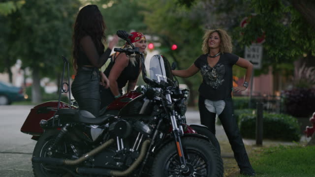 vidéos et rushes de slow motion shot of women high-fiving near motorcycles / payson, utah, united states - cadrage aux genoux