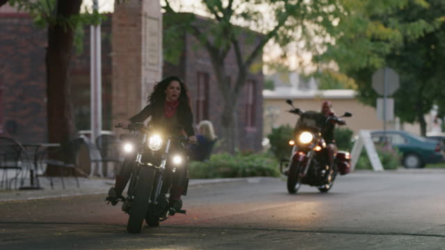 Slow motion shot of women riding motorcycles then parking / Payson, Utah, United States