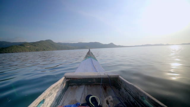 slow motion shot of wooden boat moving towards mountains while sailing on sea against blue sky, nautical vessel on water during sunny day - lombok, bali - nautical vessel点の映像素材/bロール