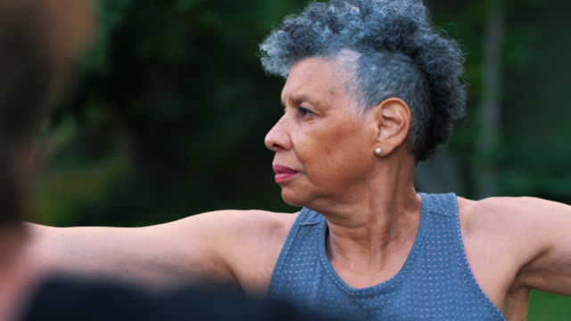 slow motion shot of wrinkled senior woman exercising in park - grey hair stock videos & royalty-free footage