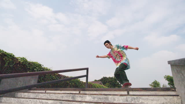 slow motion shot of young asian man skateboarding jumping in skate park day time - jumping stock videos & royalty-free footage