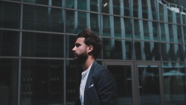 vídeos de stock e filmes b-roll de slow motion shot of young business man walking in city - caminho adiante