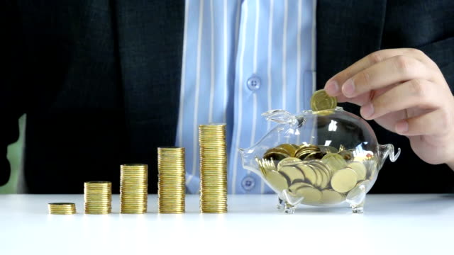 slow motion shot of young businessman drop golden coin into piggy bank glass for saving money to investment in the future - moneta video stock e b–roll