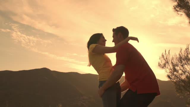 Slow motion shot of young couple dancing and hugging overlooking mountain.