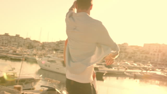 vidéos et rushes de slow motion shot of young couple running  and dancing by marina in sunset. - slow