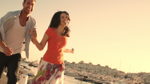 Slow motion shot of young couple running by marina in sunset.