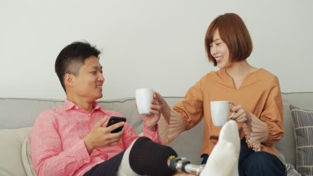 彼氏にお茶を持ってくる若い日本人女性のスローモーション撮影 - デート点の映像素材/bロール