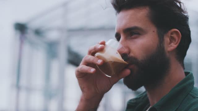 vidéos et rushes de slow motion shot of young man drinking from coffee cup - pilosité faciale