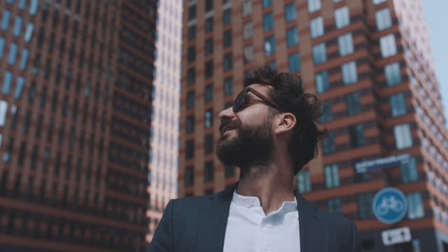 slow motion shot of young man looking to high-rise buildings in city - looking up stock videos & royalty-free footage