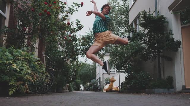 slow motion shot of young man with headphones dancing in alley - dansa balett bildbanksvideor och videomaterial från bakom kulisserna