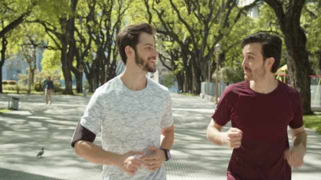 slow motion shot of young men jogging in plaza san martín, buenos aires - two people stock videos & royalty-free footage