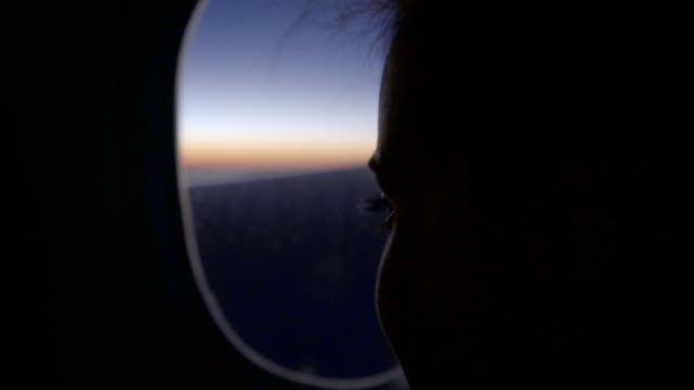 slow motion shot of young woman looking airplane through during sunset, close-up of thoughtful female passenger - new york city, new york - looking through window stock videos & royalty-free footage