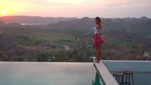 slow motion shot of young woman standing by infinity pool against sky during sunset - bali, kuta - bali stock videos & royalty-free footage