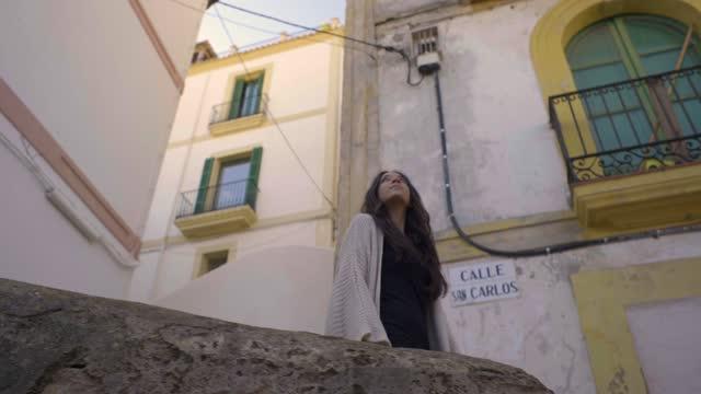 vídeos y material grabado en eventos de stock de slow motion shot of young woman walking in the old town, ibiza - vista de ángulo bajo