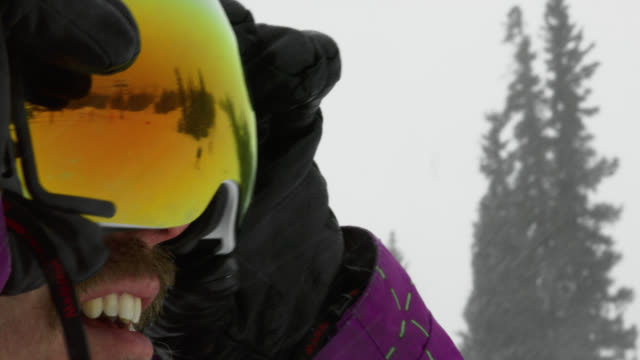 slow motion shot thirty-something, male snowboarder smiles and puts on his goggles in preparation for snowboarding on an overcast winter day - sunny stock videos & royalty-free footage