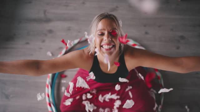 slow motion shot, woman sitting in hula hoops enjoying falling petals - blütenblatt stock-videos und b-roll-filmmaterial
