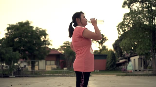 slow motion shot woman standing drink water with bottle