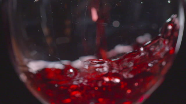 slow motion shots of red wine being poured into glass - wine glass stock videos and b-roll footage