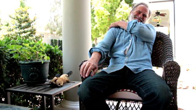 slow motion shoulder pain on veranda - pain stock videos & royalty-free footage