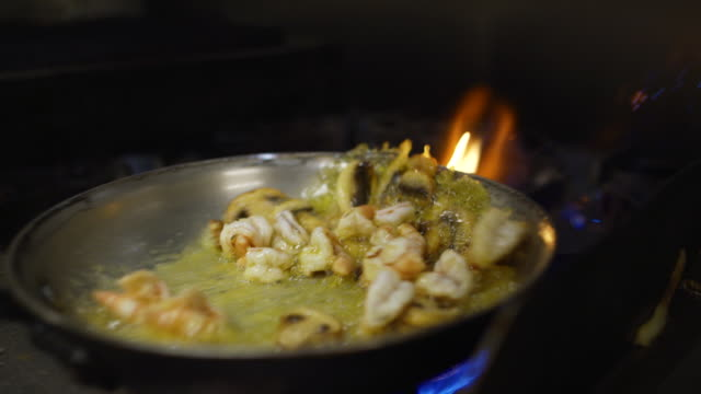 vídeos de stock e filmes b-roll de slow motion shrimp and mushroom flambe in pan of oil in commercial kitchen - camarão