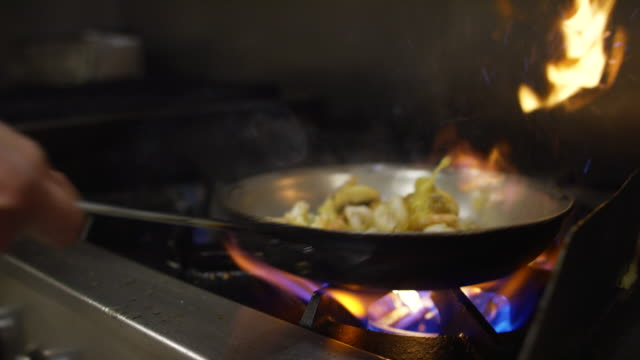 vídeos de stock e filmes b-roll de slow motion shrimp and mushroom flambe in pan of oil in commercial kitchen - marisco