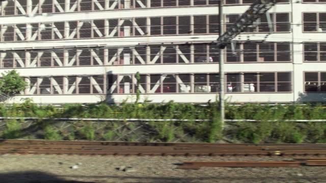 slow motion. side point of view. shot of passenger train scenery. tokyo, japan - 立体駐車場点の映像素材/bロール