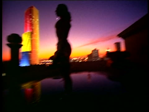 slow motion siilhouette man lifting dumbbells on roof at sunset / lights on centrust tower in background / miami - arm curl stock videos and b-roll footage