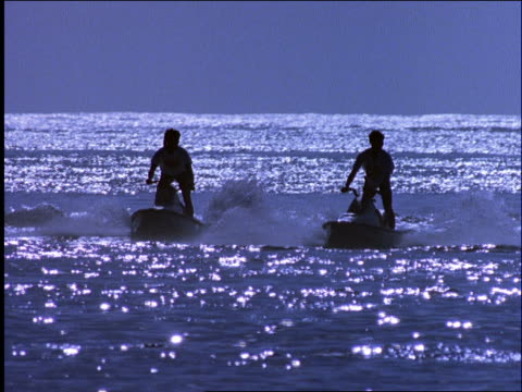 slow motion silhouette 2 men ride jet boats on ocean / 3rd man appears / nusa dua beach / baii, indonesia - acquascooter video stock e b–roll
