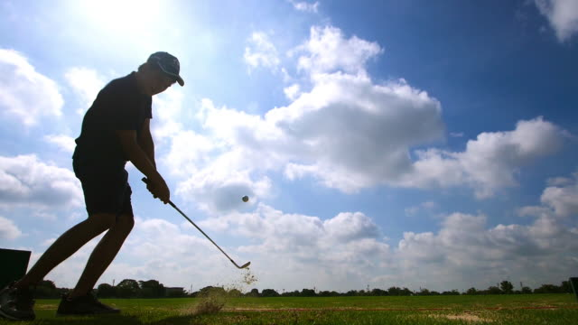 slow motion: silhouette asian young man hitting golf ball at golf course player exercise for good health - golf swing silhouette stock videos & royalty-free footage
