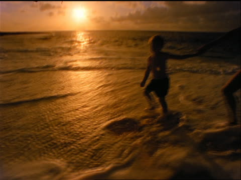 slow motion silhouette boy holding hands + leading pregnant mother wearing bikini on beach at sunset - ワンピース型の水着点の映像素材/bロール