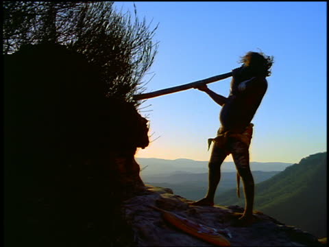 slow motion SILHOUETTE male Aborigine playing a didgeridoo / mountains in background / Blue Mountains, Australia