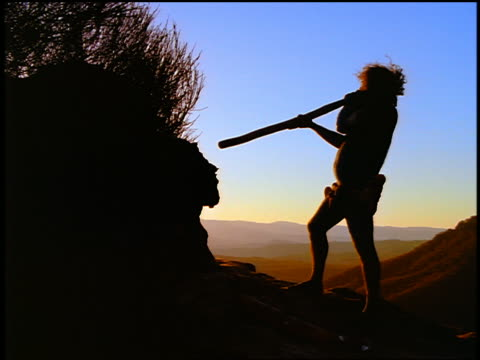 slow motion silhouette male aborigine playing a didgeridoo / mountains in background / blue mountains, australia - australian aboriginal culture stock videos and b-roll footage