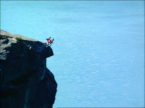 slow motion silhouette of 3 people base jumping off cliff towards water below / stavanger, norway - stunt person stock videos & royalty-free footage