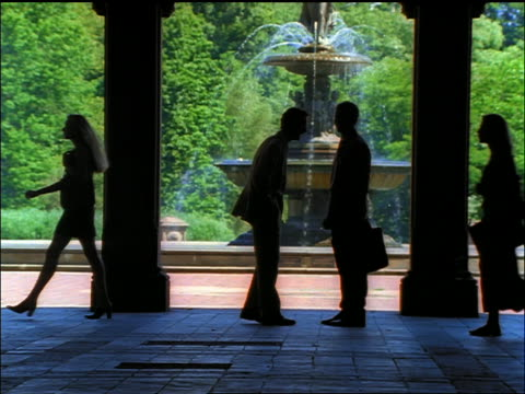 vídeos de stock e filmes b-roll de slow motion silhouette of businessmen talking under arches / fountain in central park in background - fonte bethesda