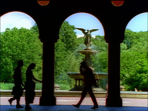 vídeos de stock e filmes b-roll de slow motion silhouette of businesspeople walking under arches / fountain in central park in background - fonte bethesda