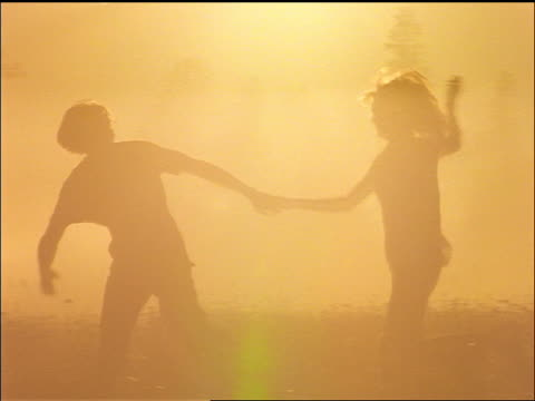 slow motion silhouette of couple running in field holding hands / sun rays in background / Montana