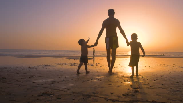 slow motion - silhouette of father and son playing together in the beach at sunset - silvestre stock videos & royalty-free footage