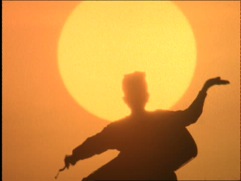 slow motion silhouette of man dancing + playing drum at sunset / kuta beach, lombok island / indonesia - anno 1997 video stock e b–roll