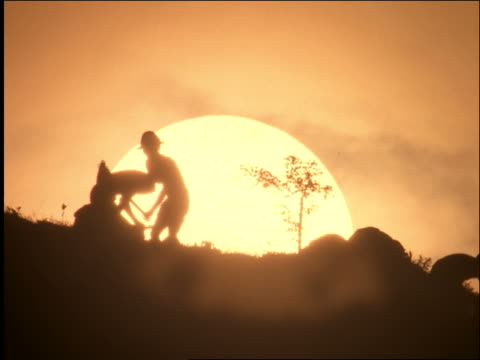 slow motion silhouette of men using hoes in dirt / west java / indonesia - plowing stock videos & royalty-free footage