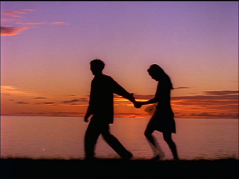 stockvideo's en b-roll-footage met slow motion pan silhouette of teen couple holding hands + walking by ocean at sunset - romance