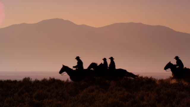 Slow motion silhouette shot of group of cowboys riding horses.