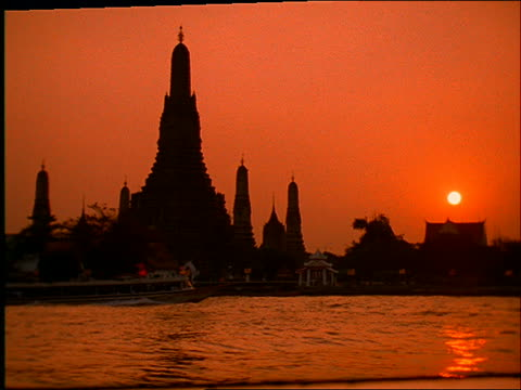 slow motion silhouetted buddhist temple (wat arun) with boats on chao phraya river in foreground / sunset / bangkok - romantische stimmung stock-videos und b-roll-filmmaterial