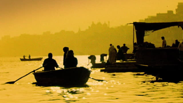 Slow motion silhouetted people in rowboat and on bank of Ganges River / Varanasi, India