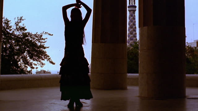 slow motion silhouetted woman dancing flamenco next to large columns in parc guell / barcelona, spain - flamenco dancing stock videos and b-roll footage
