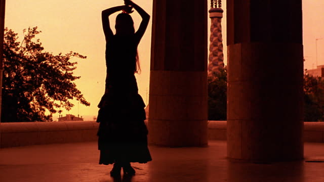 orange slow motion silhouetted woman dancing flamenco next to large columns in parc guell / barcelona - flamenco dancing stock videos and b-roll footage