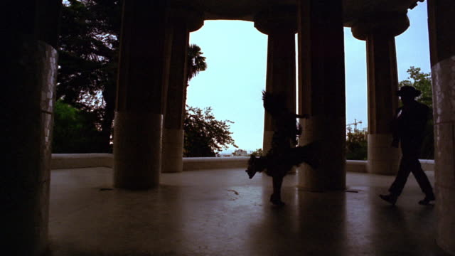 slow motion silhouetted woman spinning between large columns + man following with guitar / parc guell - spanish culture stock videos & royalty-free footage