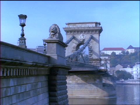 blue slow motion slight pan chain bridge over danube river / budapest, hungary - ponte con catene ponte sospeso video stock e b–roll