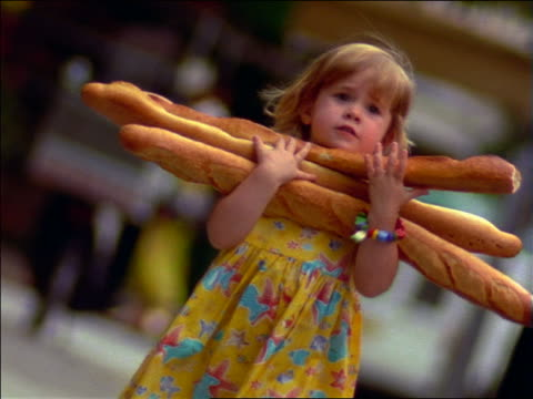 vídeos de stock e filmes b-roll de slow motion small girl with armload of baguettes walking toward camera / paris, france - cultura francesa