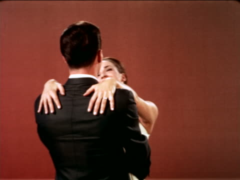 vidéos et rushes de 1967 slow motion smiling woman with long brown hair hugging man in studio / industrial - 1967