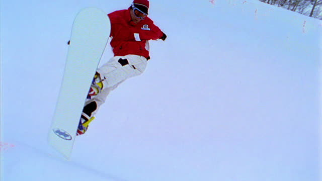 OVEREXPOSED slow motion PAN snowboarder jumping on half pipe then wiping out